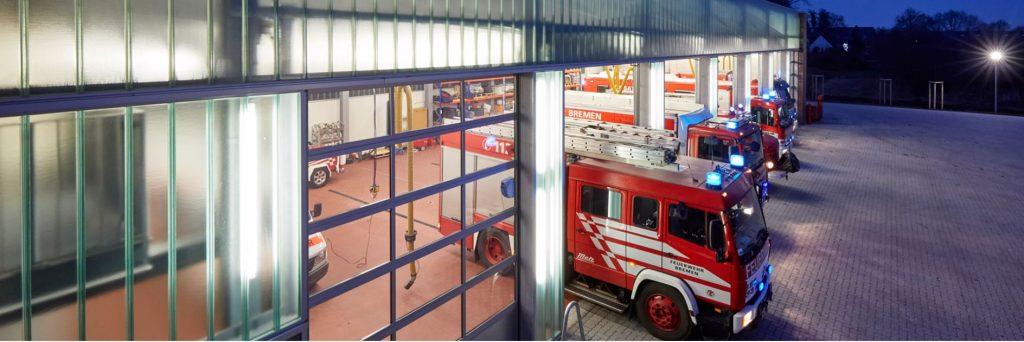 3 Feuerwehrautos in einer Halle